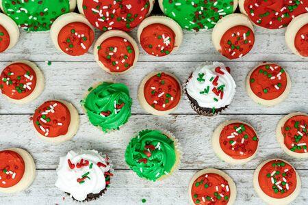 Vista superior plana de golosinas navideñas: cupcakes y galletas de azúcar de crema de mantequilla con chispas Foto de archivo