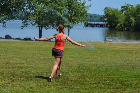 Young adult woman runs through the sprinklers in the park in the summer. Concept for carefree living