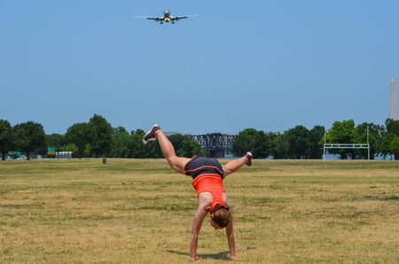 Young adult woman attempts to do a cartwheel in a park, but fails. Airplane and Washington Monument in the background.