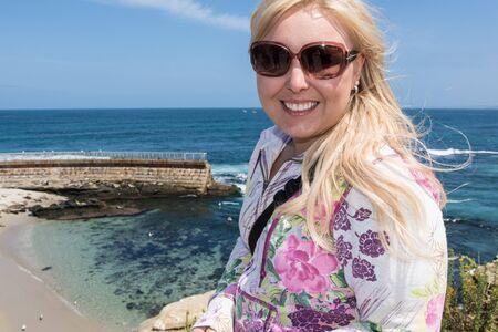 Blonde female explores the rugged, rocky beach of La Jolla California Stock Photo