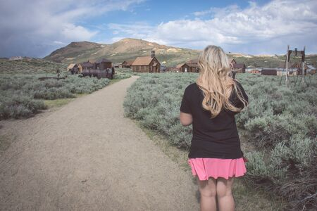 A blonde female walks on a path toward more abandoned buildings in the ghost town of Bodie California Banque d'images