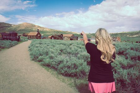 A blonde female tourist points to more abandoned buildings in the ghost town of Bodie California