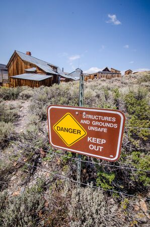 Sign warning visitors to Bodie State Historic Park in California to keep out of unstable structures and grounds 免版税图像