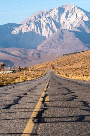 View of the Eastern Sierra Nevada mountain range in California taken in the middle of an open road/highway on a sunny autumn morning Stock Photo
