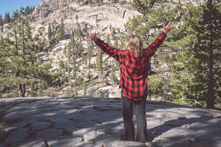 A mature blonde woman wearing a buffalo plaid flannel shirt (red and black) raises arms up in the Eastern Sierra Nevada mountains in California, on top of Devil's Postpile National Monument