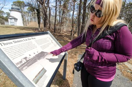 Cape Cod, MA - April 4, 2018: A blonde tourists learns and discovers information on the Three Sisters Lighthouses on Cape Cod on a spring day 免版税图像