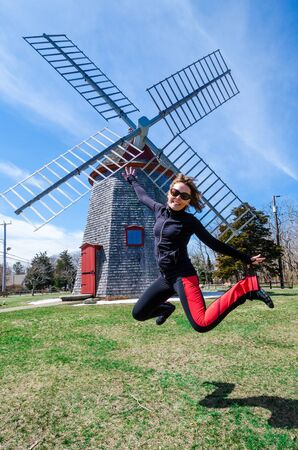 Woman jumping in front of the Eastham Windmill. The historic old fashioned mill sits in a Cape Cod Park in Massachusetts. Fisheye lens view