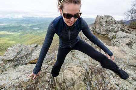 Woman hiker and rock climber concentrates on scrambling up a steep section of rock outcroppings in Shenandoah National Park Banco de Imagens