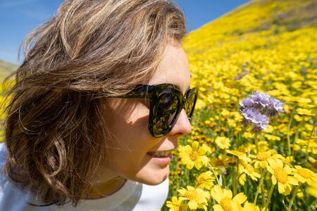 Adult female woman stops to smell the beautiful yellow wildflowers. Concept for springtime allergies