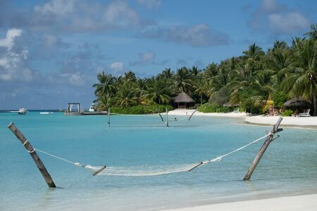 North Male Atoll, Maldives - November 23, 2019: Resort with hammocks, volleyball nets, palm trees and crystal clear blue water in the Maldives, a tropical vacation destination Standard-Bild
