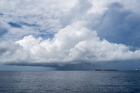 Large severe thunderstorm storm cloud forms over the Maldives on the Indian Ocean Stock Photo