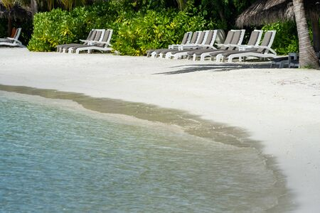 Empty lounge beach chairs on the white sand beach of a resort in the Maldives 스톡 콘텐츠 - 135985494