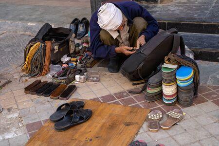 New Delhi, India - November 17, 2019: Indian craftsman (cobbler) fixes a broken zipper on a backpack in a market Stock Photo