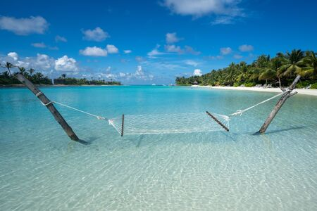 Empty hammock in the shallow, turquoise tropical waters of the Maldives on a beach