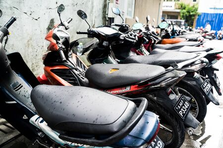 Male, Maldives - November 26, 2019: Row of motorbikes or motorcycles, parked along the side of a road. This is the main mode of transportation on the Maldivian island Standard-Bild
