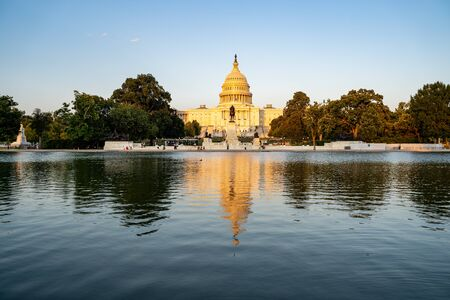 United States Capitol building at dusk sunset during a summer day, glowing from sunshine, with reflecting pond