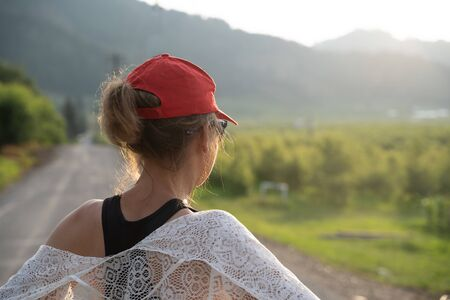 Woman wearing a red ballcap and a white lace shawl looks out on the rural landscape during the golden hour. Concept for dreaming, thinking, admiring
