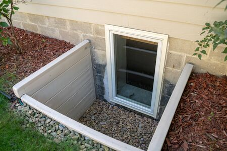 Exterior view of an egress window in a basement bedroom. These windows are required as part of the USA fire code for basement bedrooms Foto de archivo