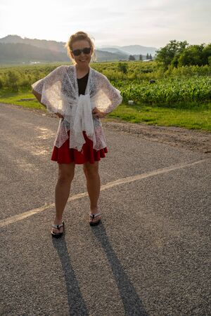 Beautiful woman wearing a white lace shawl and America USA sunglasses poses on a road in rural america