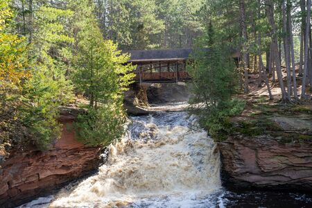 Amnicon Falls State Park waterfall with a covered bridge, over the Amnicon River in Northern Wisconsin Stock fotó