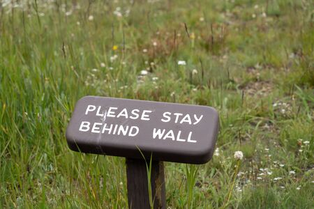 Sign in Olympic National Park reminding hikers to stay behind the wall at Hurricane Ridge
