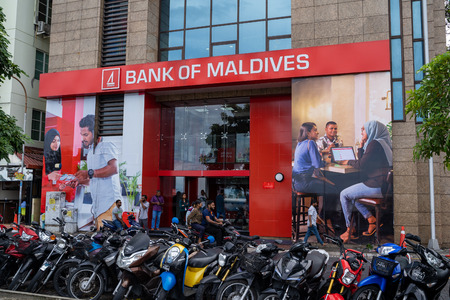 Male, Maldives - November 26, 2019: Exterior view of the Bank of Maldives, motorbikes parked outside the financial insitituion 스톡 콘텐츠 - 136065340