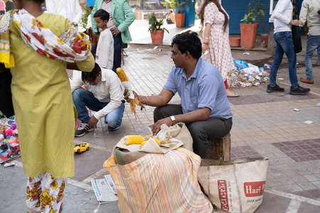 New Delhi, India - November 17, 2019: Street food vendor cooks and serves corn on the cob to hungry customers at Nehru Place market