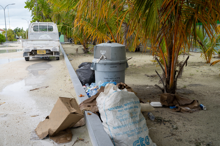 Maafushi Island, Maldives - November 26, 2019: Litter and overflowing garbage cans along the side of the road on the Maldivian Island. Concept for pollution and single use plastic bottles