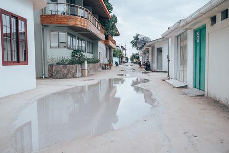 Maafushi Island, Maldives - November 26, 2019: Flooded sandy roads with huge puddles after a rainstorms, along the streets of Maafushi Island 에디토리얼