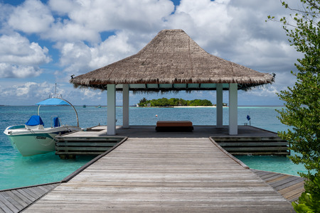 North Male Atoll, Maldives - November 23, 2019: Resort with a hut over a dock and crystal clear blue water in the Maldives, a tropical vacation destination Editöryel