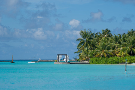 North Male Atoll, Maldives - November 23, 2019: Resort with amenities, palm trees and crystal clear blue water in the Maldives, a tropical vacation destination
