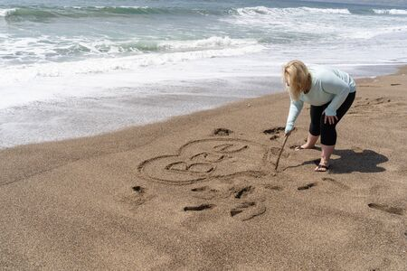 Blonde woman writes Bae (slang for Before Anyone Else, representing a romantic relationship) in sand on the beach