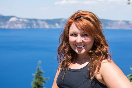 Redheaded female with long hair poses in front of the bright blue water of Crater Lake National Park