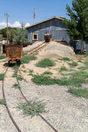 Old abandoned mining equipment cart leads into an ore processing mill in Laws, California 스톡 콘텐츠