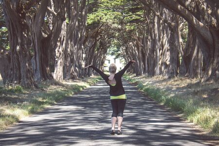 Blonde female raises arms up at the Cypress Tree Tunnel on Point Reyes National Seashore in Marin County in Northern California