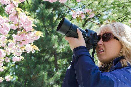 Attractive blond female photographer concentrates, taking photos with a zoom lens on a digital dslr camera outdoors