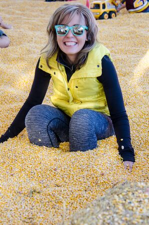 Adult female sits down in a corn pit with yellow corn kernels