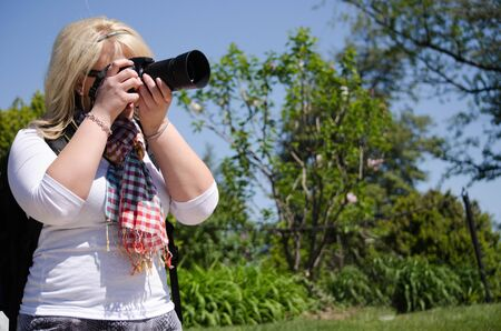 Attractive blond female professional photographer concentrates, taking photos with a zoom lens on a digital dslr camera outdoors
