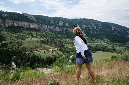 Blonde female photographer attemps to take a picture with her camera of the scenery of Wyoming Beartooth Highway