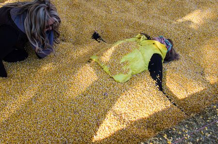 An adult female gets buried by another female friend in corn kernels in a corn pit,
