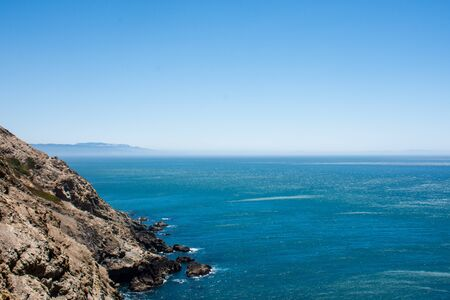 Oceanside cliffs at Point Reyes National Seashore in Marin County, California. Bright blue color of the Pacific Ocean, on a sunny day, with extra copyspace