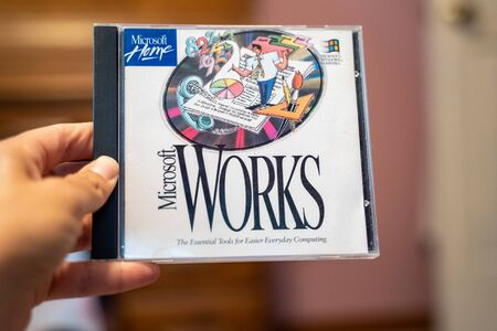 Scandia, MN - September 10, 2019: Hand holds up a CD ROM of Microsoft Works, a spreadsheet and word processing software from the 1990s 版權商用圖片 - 138049682