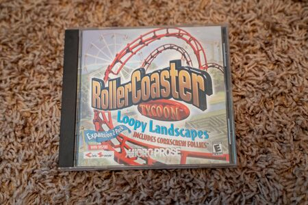 Scandia, MN - September 10, 2019: CD-ROM computer software game of Rollercoaster Tycoon Loopy Landscapes expansion pack. This was a theme park simulation game 新聞圖片