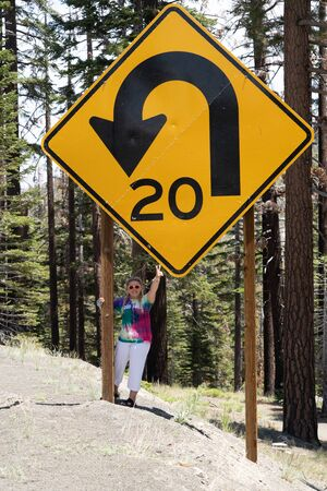 An adult woman stands next to a giant road sign in Mammoth Lakes, California, showing the scale of the size of the sign. Giving peace sign Stock Photo
