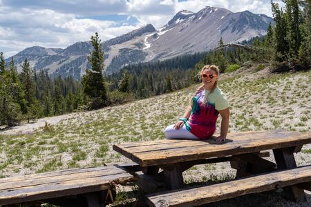 Beautiful blond woman sits on a picnic table at the Minaret Vista viewpoint in Mammoth Lakes California, wearing a tie dye tshirt and sunglasses Stock Photo