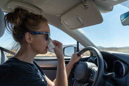 Woman female driver uses a tissue to blow her nose while driving. Concept for distracted driving, multi tasking, health issues, colds, sick, medical issues