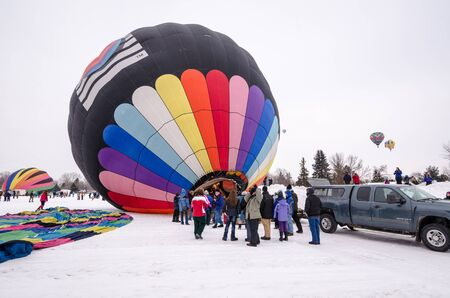Colorful hot air balloons prepare to launch at the Hudson Hot Air Affair in winter