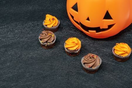 Halloween cupcake arrangement background with chocolate cupcakes and jack-o-lantern
