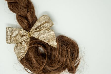 Braided brown hair (women's) tied in a glittery gold bow