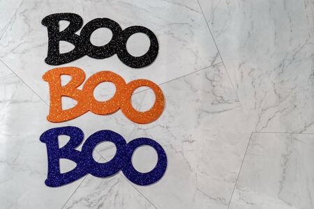 Boo word for Halloween three times, centered, isolated on marble. Glittery words in black, orange and purple